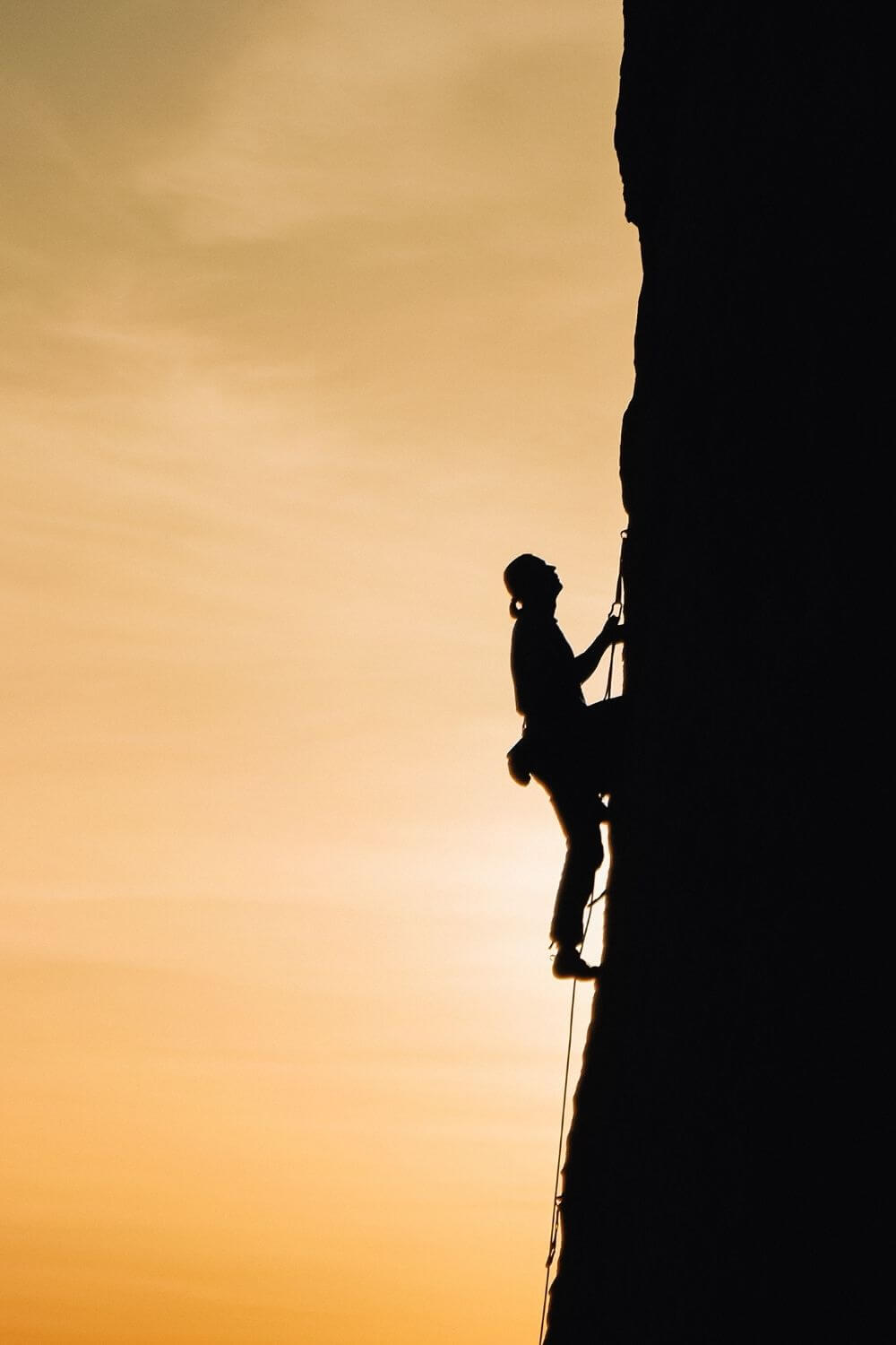 silhouette of a person climbing a mountain with orange sunset background