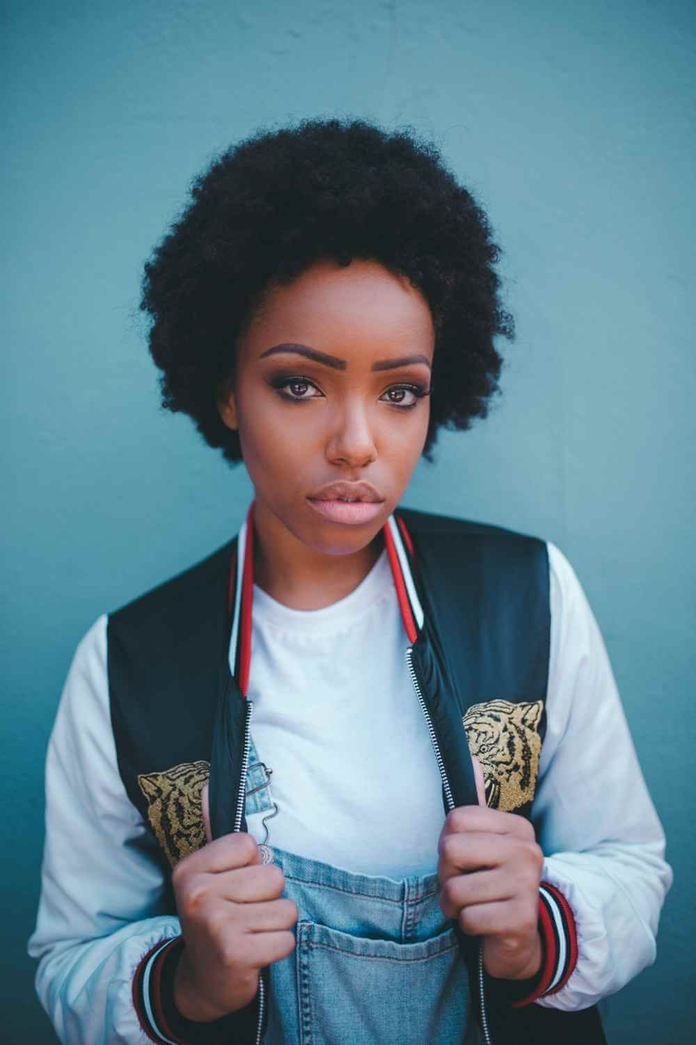 black woman with afro in front of light blue background grabbing onto her jacket